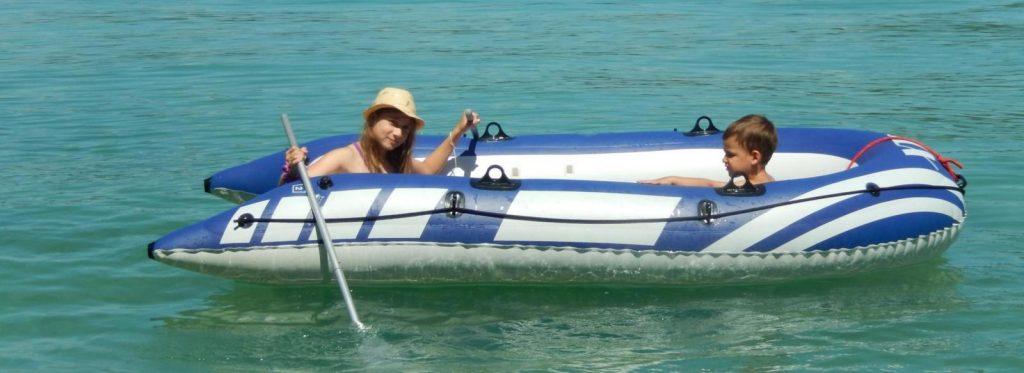 Zwei Kinder fahren im Schlauchboot am See